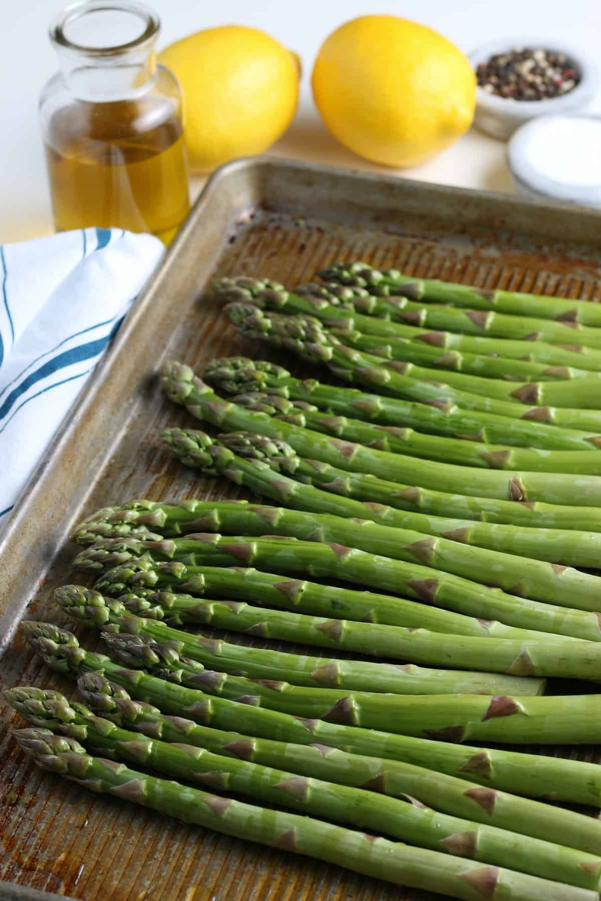 Freah prepared asparagus are laying side by side on a baking sheet to catch all of the runoff of the oil and salt and pepper when tossing.