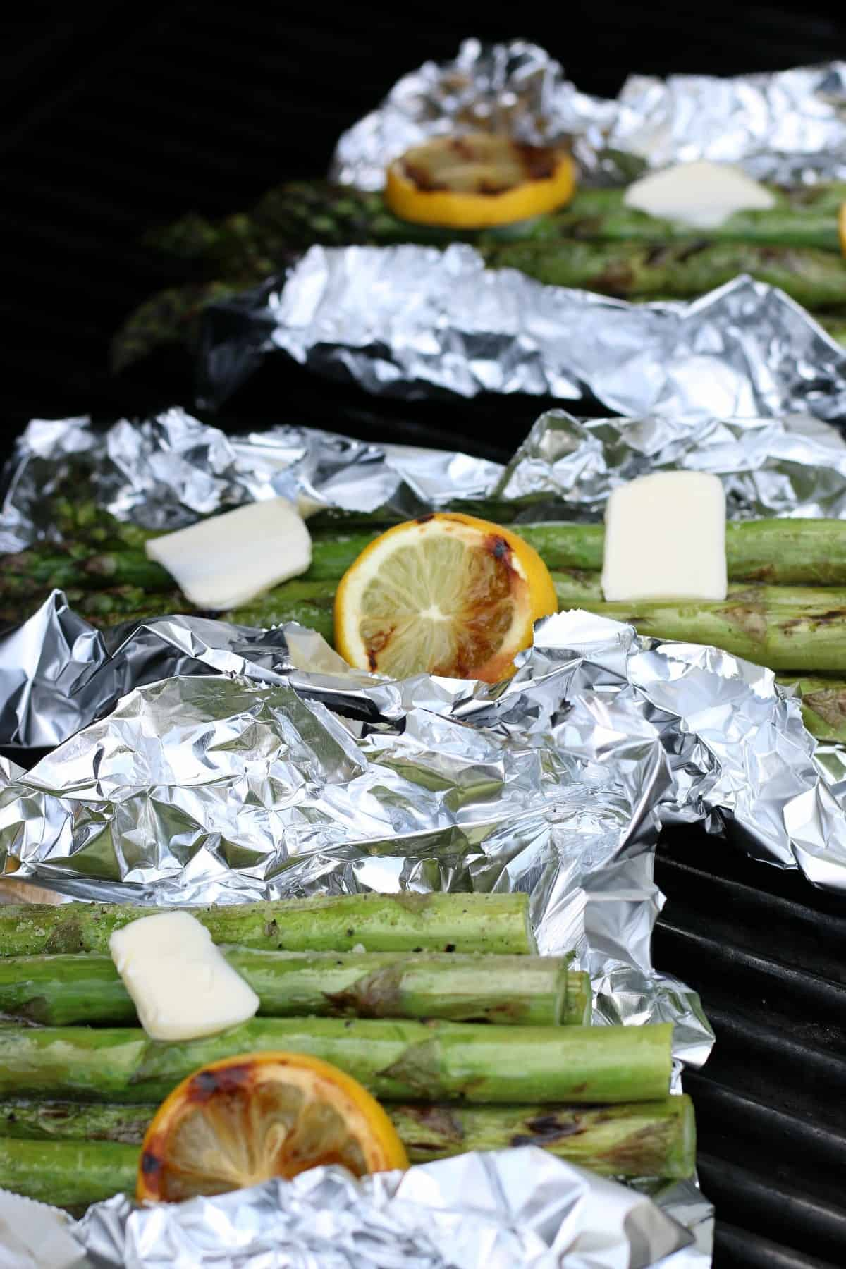 Sideways view showing open foil packets with grilled asparagus with grilled lemon and pats of dairy-free butter on top.