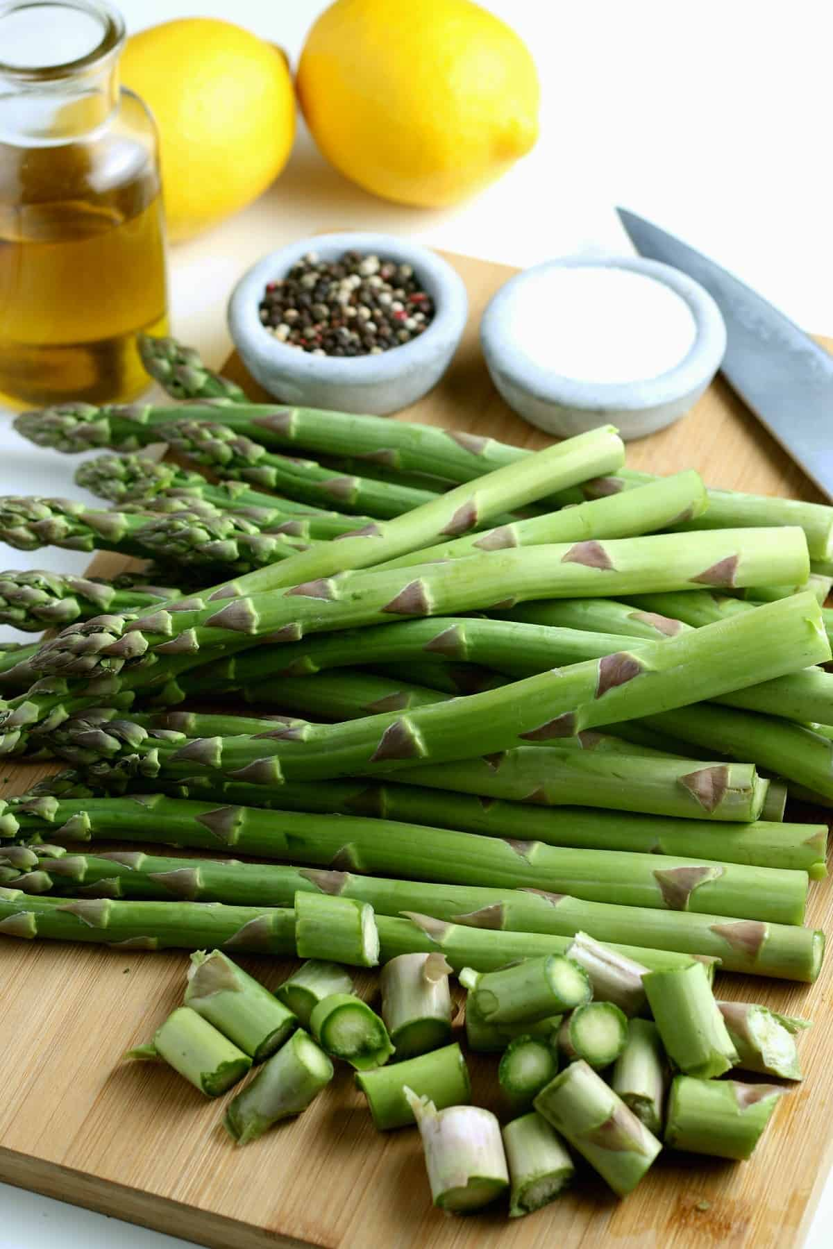 A large bunch of asparagus spears and laying on a wooden cutting board with about an inch or two cut off the large stalks.