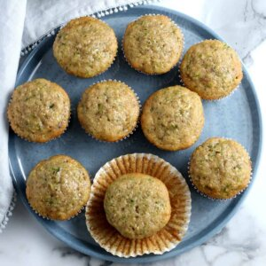 Overhead view of zucchini muffins on silverblue tray where one muffin has it's paper cup opened around it.