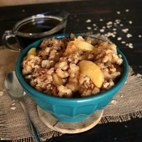A turquoise bowl is filled with apples and oats.