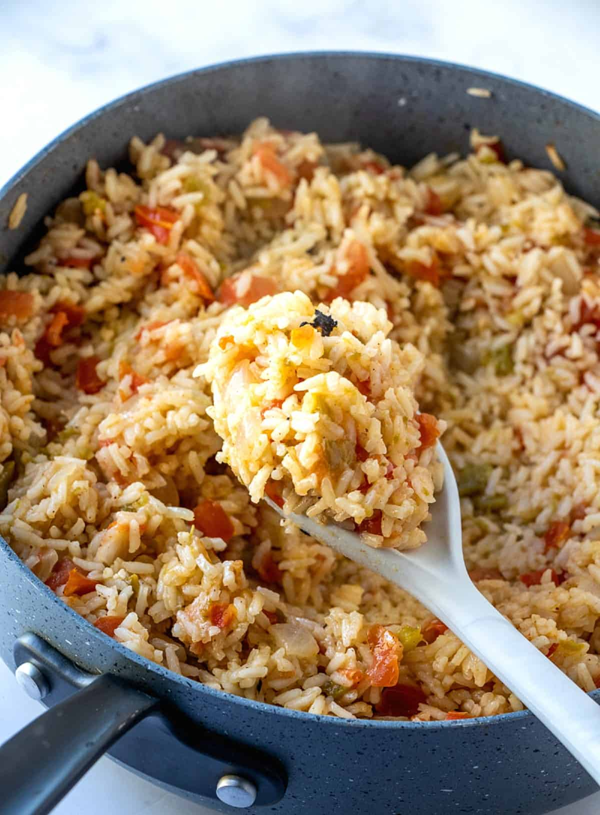 A wooden spoon has scooped up a mound of Spanish rice close to the lens so that we can see all of the ingredients inside.