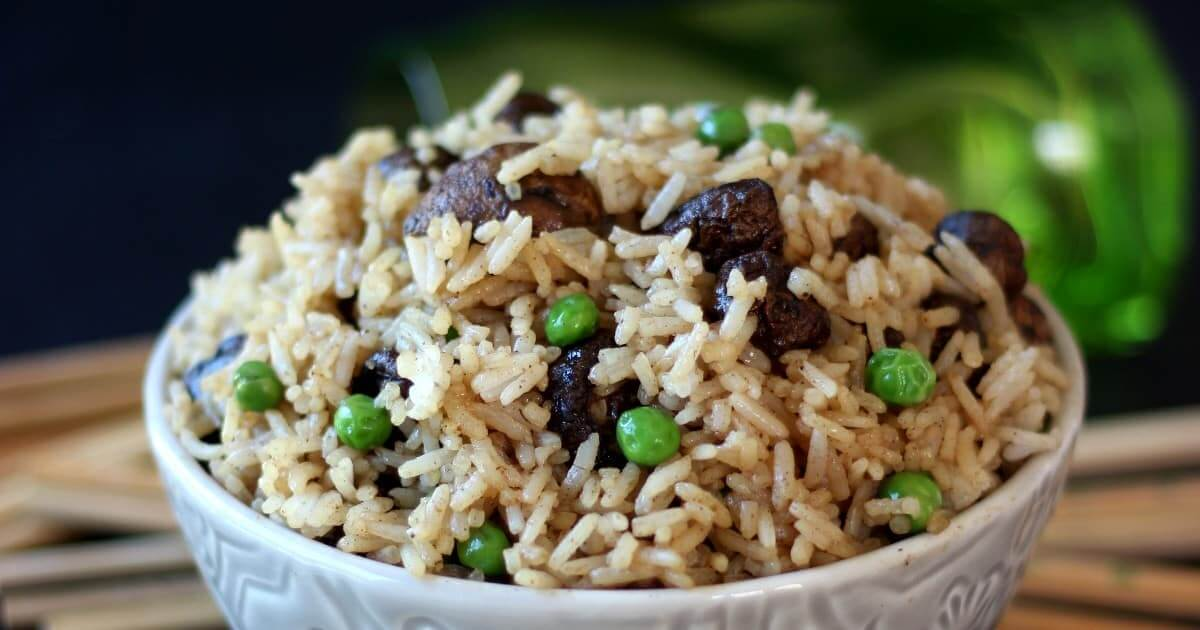 Close up wide photo with a bowl full of rice, mushrooms and peas.