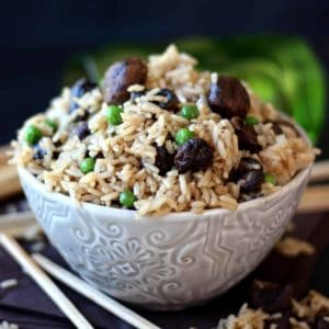 Gorgeous rice with mushrooms and peas is filling a patterned bowl with chopsticks on the side.