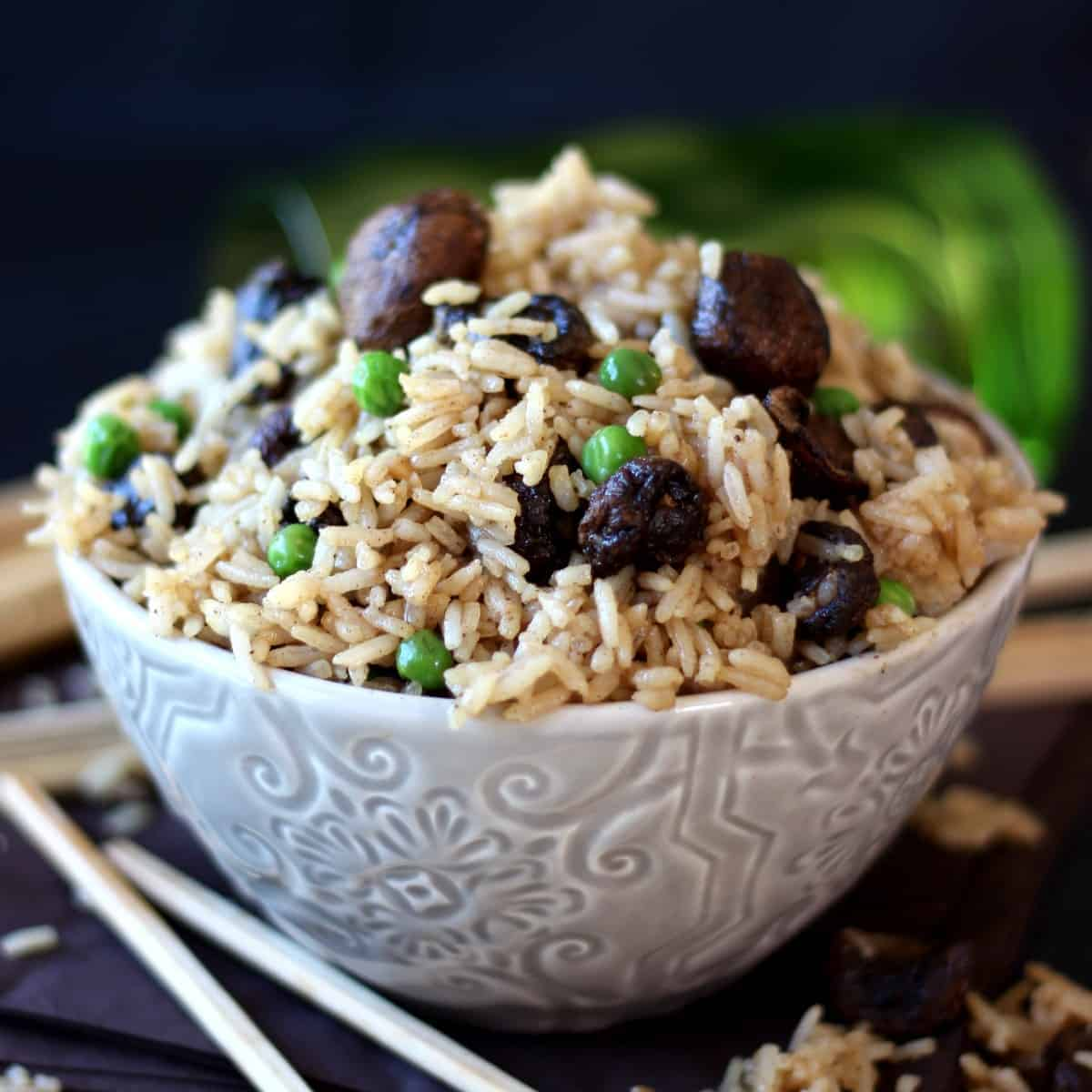 Gorgeous thai sticky rice with mushrooms and peas is filling a patterned bowl with chopsticks on the side.
