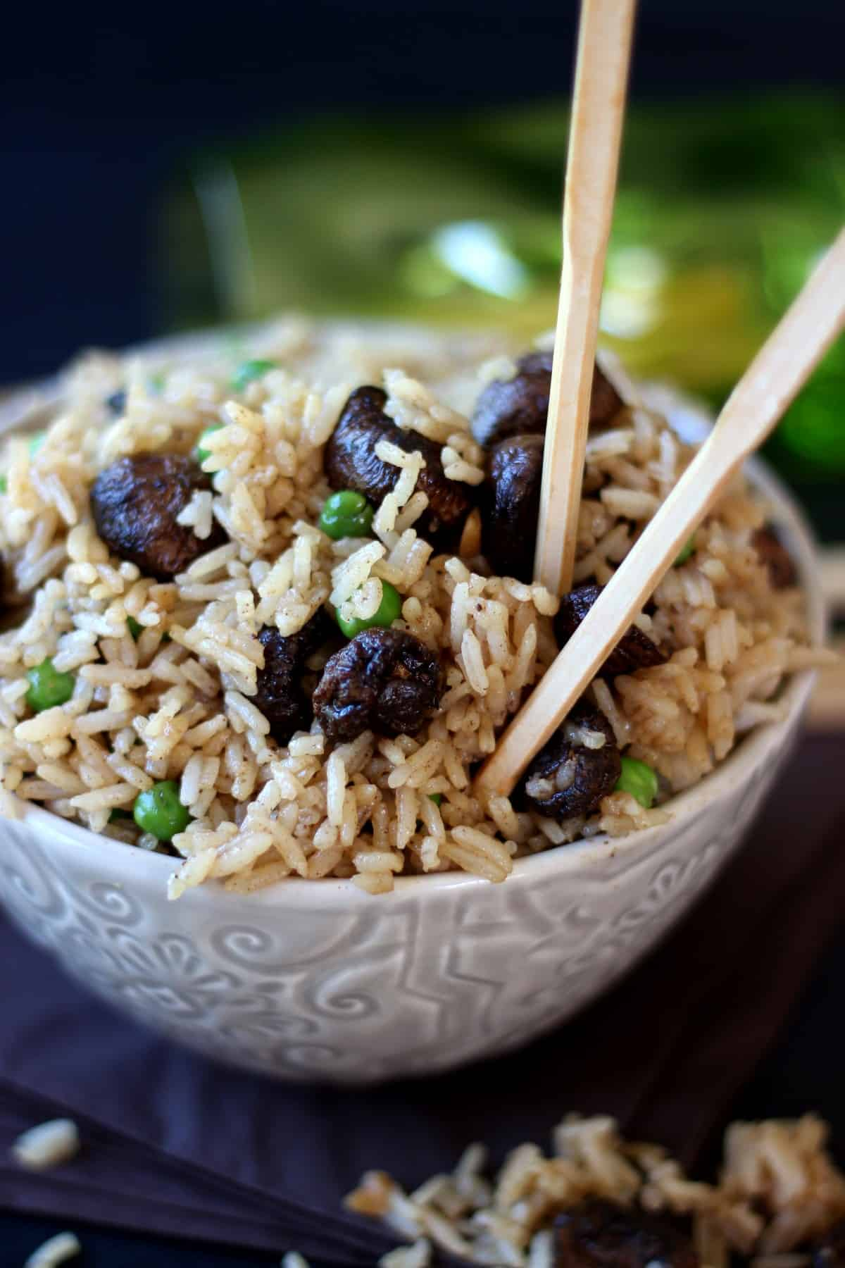 Rice, mushrooms and peas is filling a patterned bowl that's sitting on a pile of navy blue napkins. There are chopsticks sticking in the top to lift a bite.