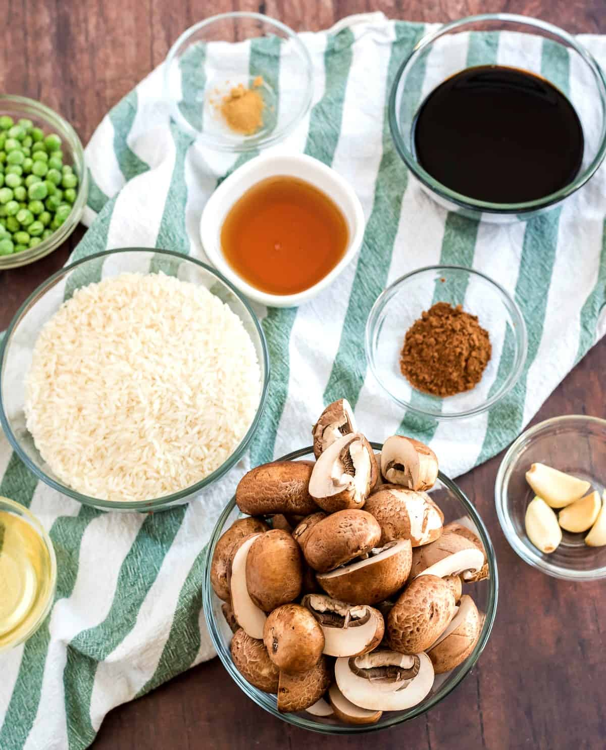 Overhead view of all of the ingredients for a comforting Asian meal are in their own small bowls and are sitting on a wooden table.