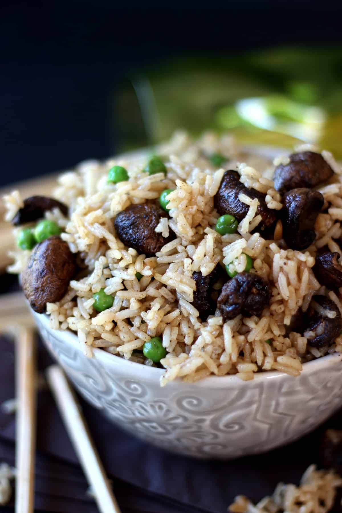 Close-up of sticky rice with mushrooms and peas filling a patterned ivory bowl with chopsticks on the side.