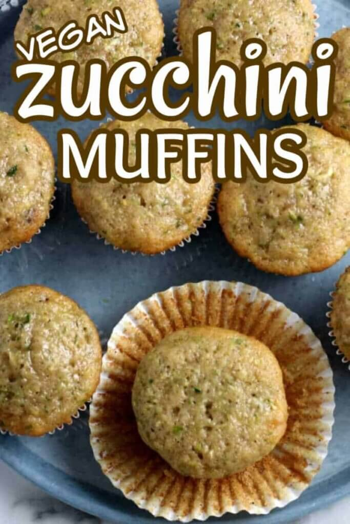 Overhead view of zucchini muffins on silverblue tray where one muffin has it's paper cup opened around it. Text above for pinning.