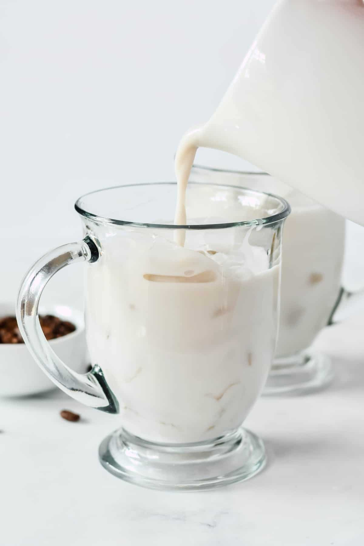 Dairy-free milk is being poured from a pitcher into a clear glass mug filled with ice.