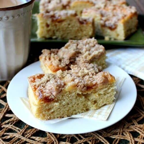 Vegan Coffee Cake with Apple Cinnamon Streusel is tilted with two slices sitting on a gold and white napkin.