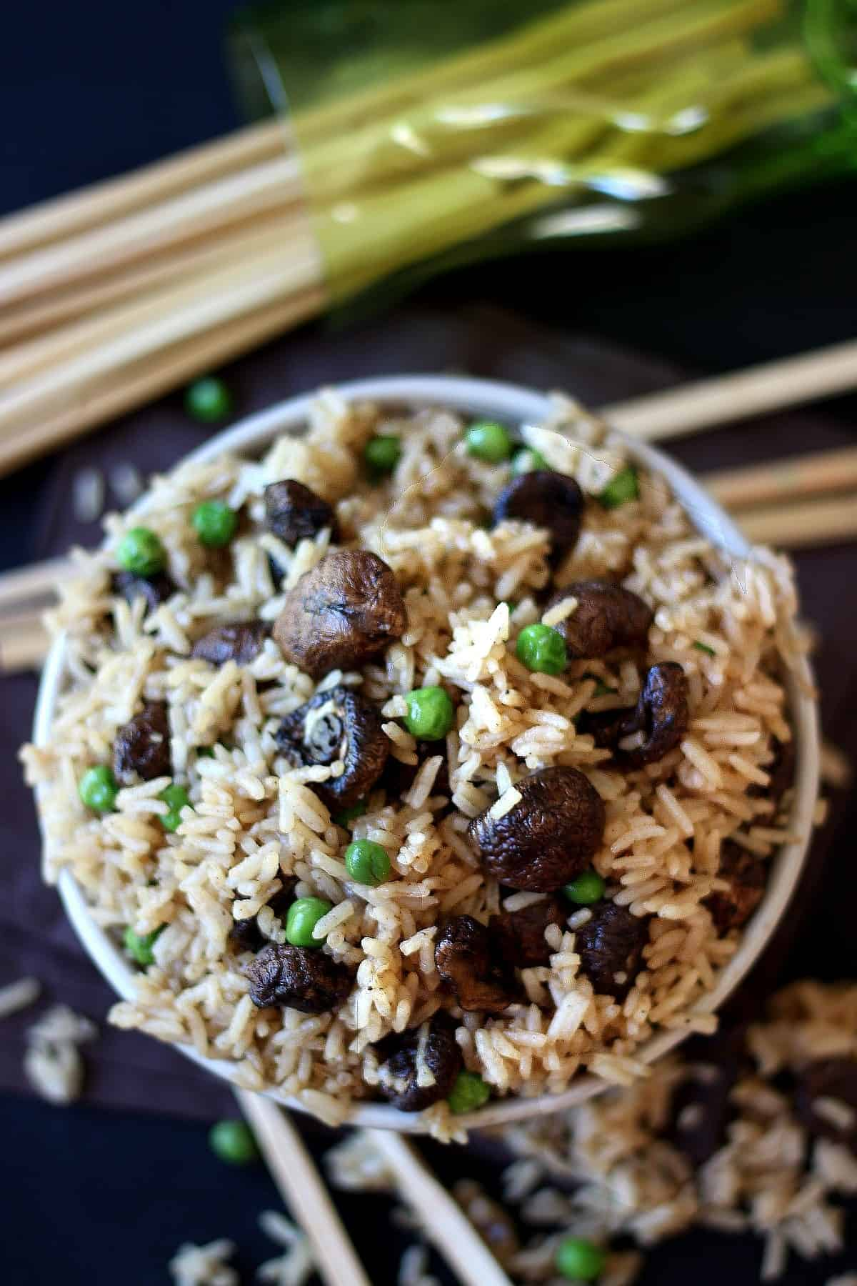 Overhead view of rice. meaty mushrooms and peas is filling a bowl to overflowing with chopsticks on the side.