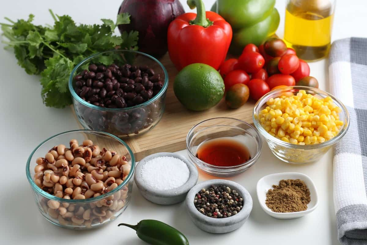 All of the ingredients for a great vegetable dip and dressing are laid out on a wooden cutting board.