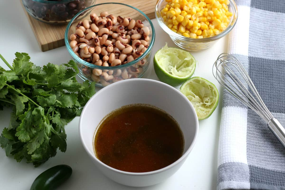 The mixed dressing is in a white bowl sitting in front of corn, black eyes peas and squeezed lime.