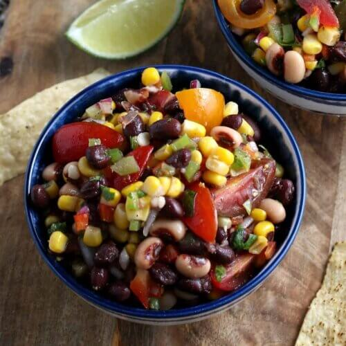 Overhead view of cowboy caviar in a blue bowl showing corn, beans and more veggies all waiting to be dipped with a chip.