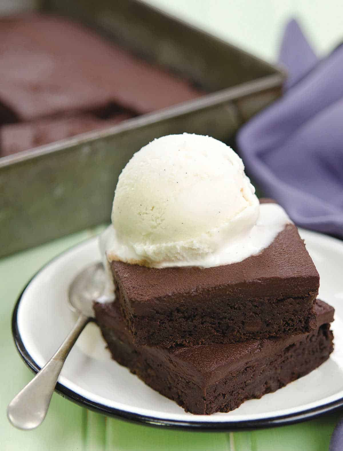 Two brownie squares stacked on top of each other with frosting and a scoop of nice cream on top.