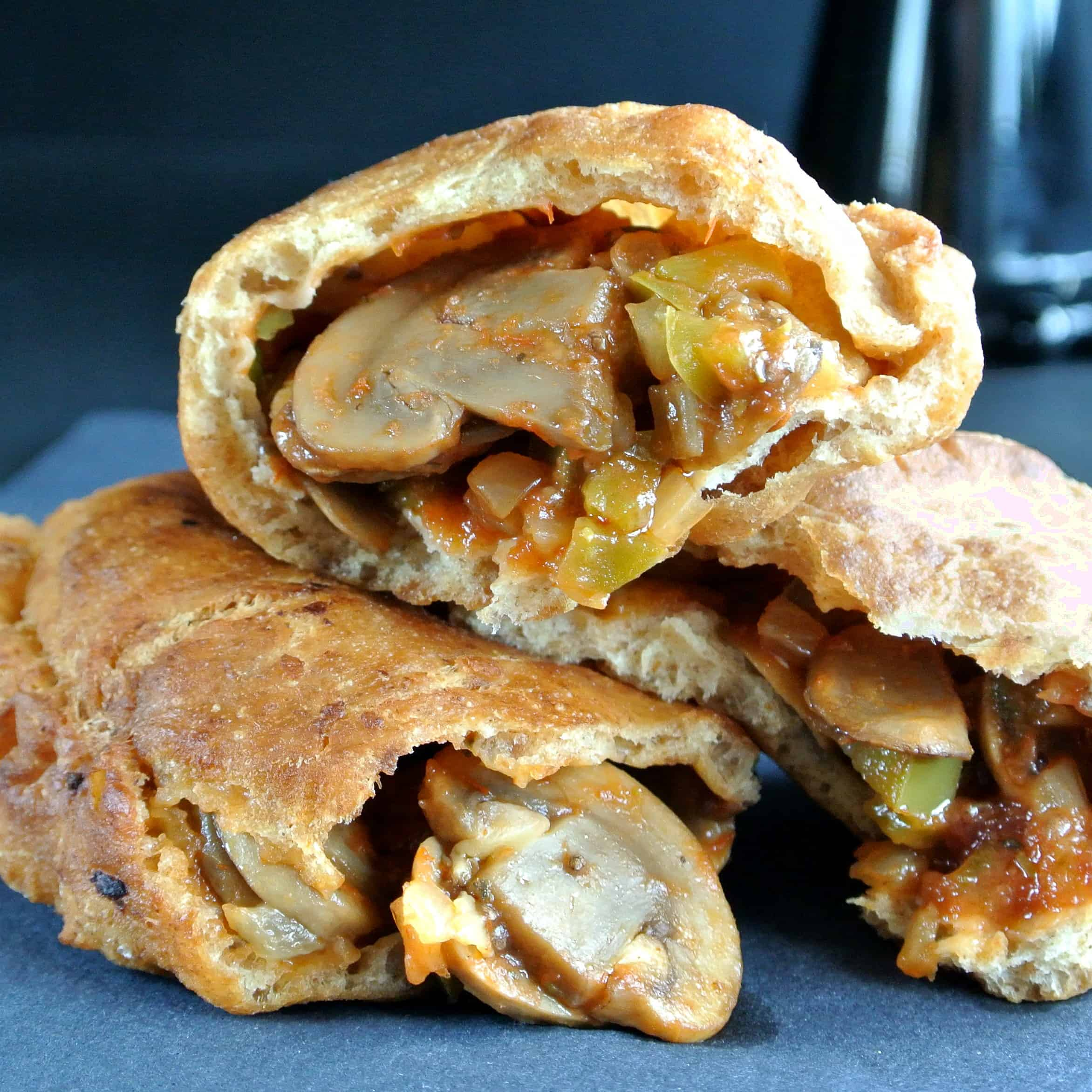 Extreme closeup photo of three savory fried dough pastries showing their mushroom filling inside.