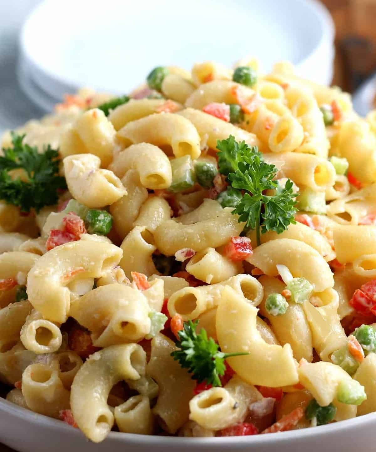 Extreme close-up of vegan macaroni salad centered and showing all of the ingredients with it's creamy dressing.