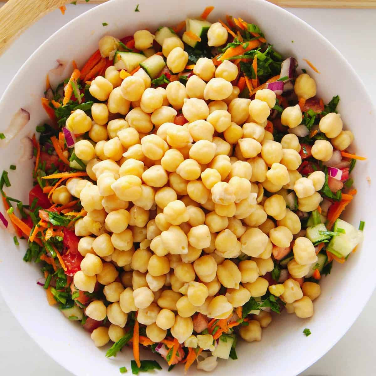 The final vegetable, canned chickpeas, is added to the salad mixture in this overhead view.