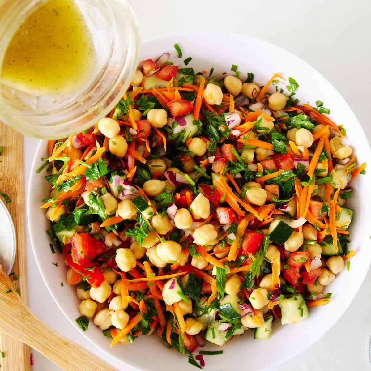Overhead view of chickpea salad with lemon dressing being poured over the top.
