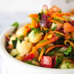 Close up sideways view of colorful Mediterranean Chickpea salad in a white bowl against a white background.