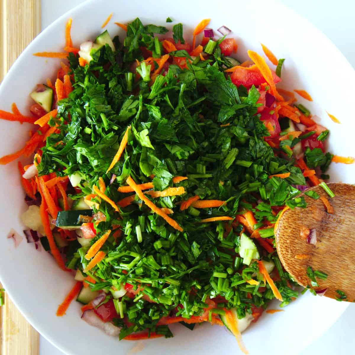 Cucumber, shredded carrot and fresh chopped parsley is added to the tomatoes and onions in an overhead shot.