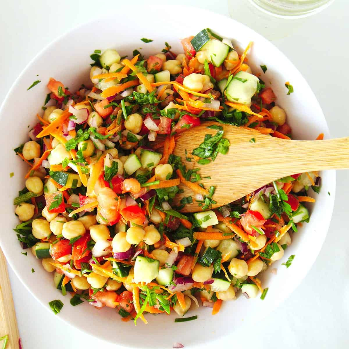 Overhead view of a mixed chickpea salad with a wooden spoon flipped over inside the white bowl.