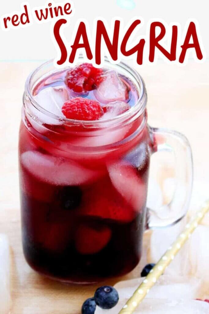 Clear glass mug is filled with dark red sangria along with berries. Red text is at the top.