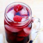 A tilted jar mug is tilted forward with red wine sangria over ice.Raspberries and blueberries are interspersed throughout.