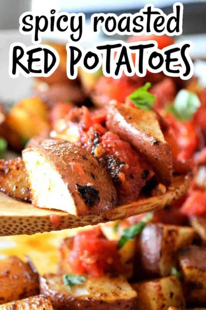Closeup photo of roasted red potatoes and tomatoes on a wooden spoon being held close to the camera.