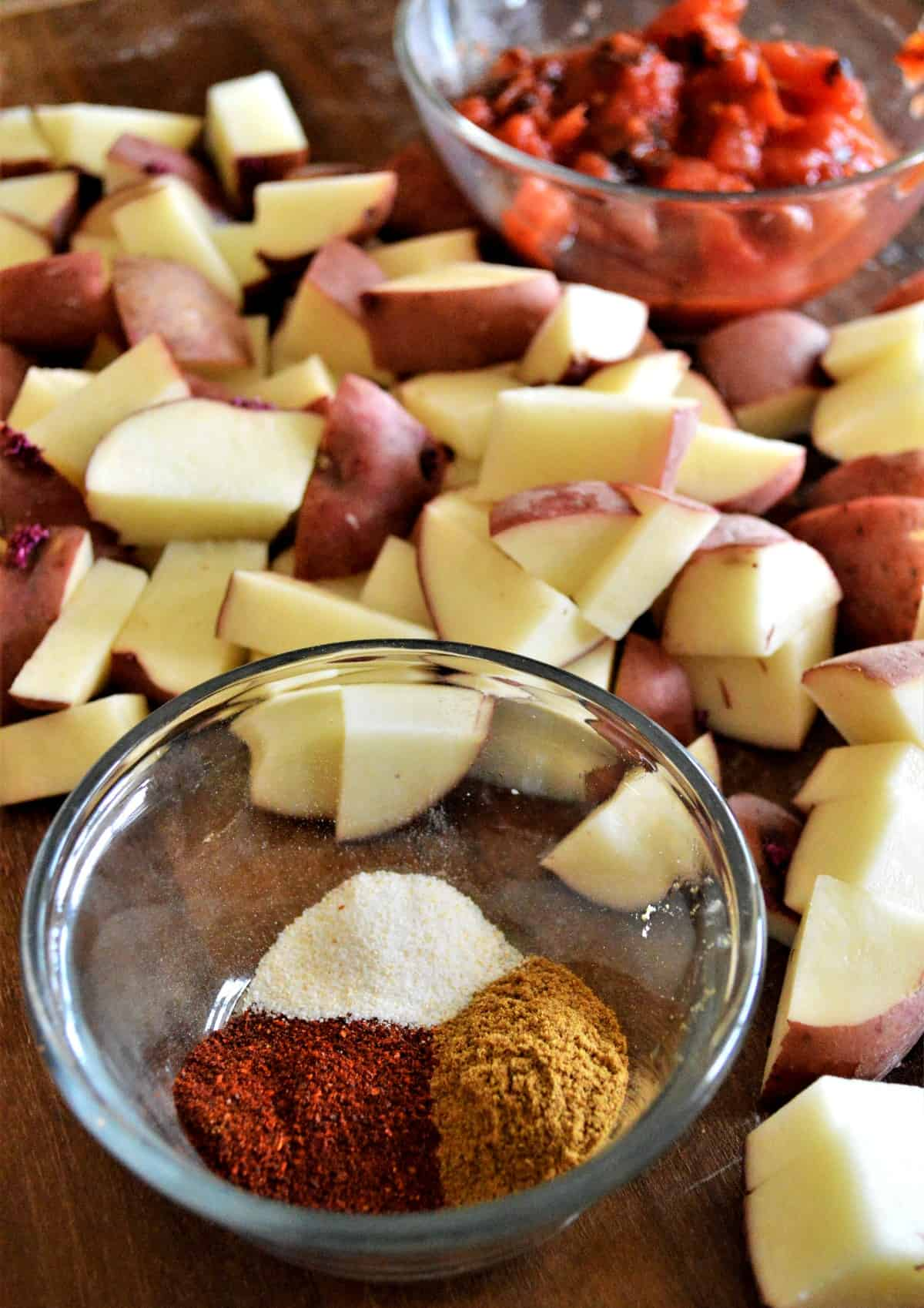 Cut red veggies in the background with a small bowl full of the recipes spices.