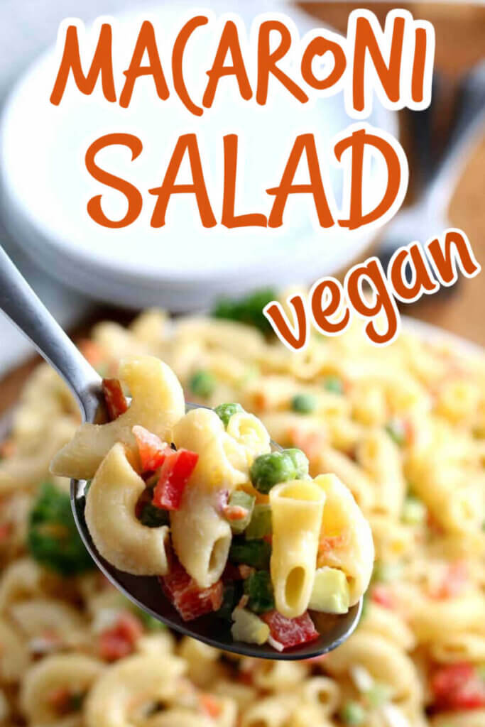 A close up bite on a spoon of vegan macaroni salad with small chopped veggies.