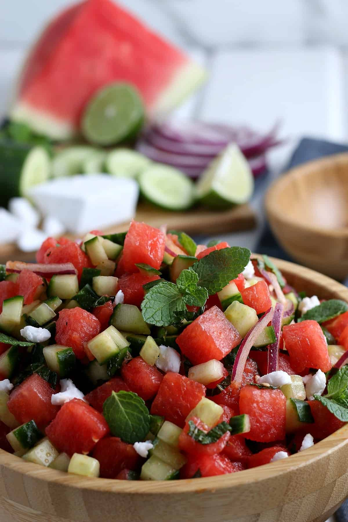 Very close-up photo of the watermelon salad in a wood bowl tossed with fresh mint and dressing. More of the same ingredients are in the background.