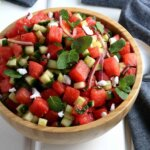 Tilted wooden bowl filled with watermelon feta salad with fresh mint and vegan feta.