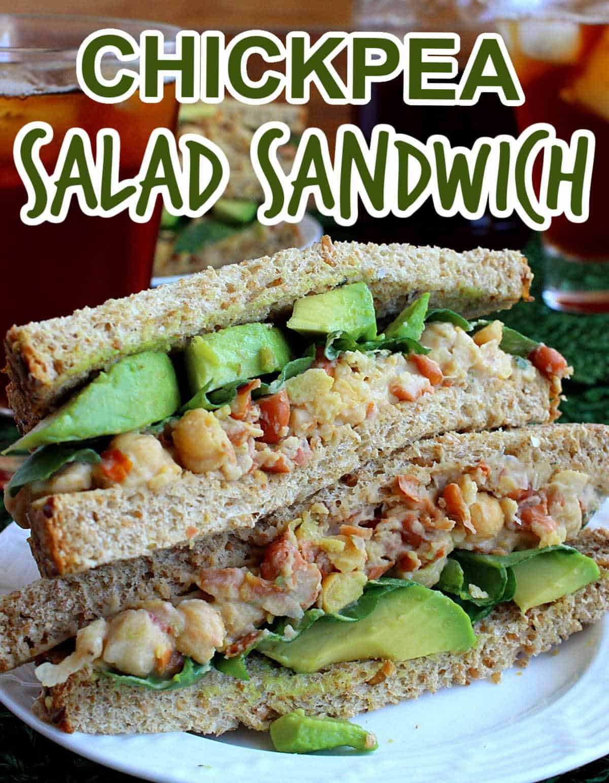 Two chickpea salad sandwich halves stacked on top of each other to show the veggies inside. Text above for pinning.