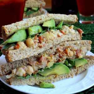 Two chickpea salad sandwich halves stacked on top of each other to show the veggies inside.