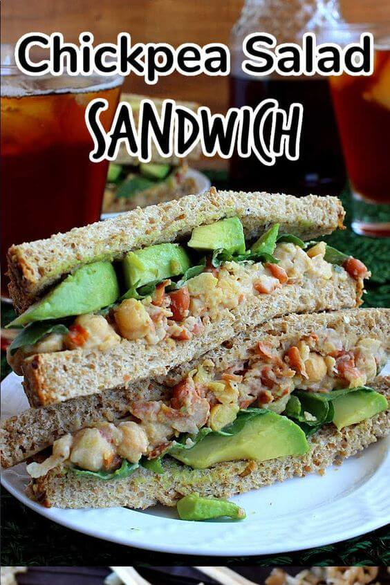 Two sandwich halves stacked on top of each otherwith avocado slices showing.