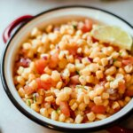 Close up bowl of chipotle corn salsa showing dice tomatoes and lime on the side.