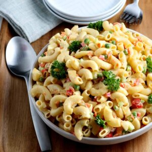 Large angles bowl full of tossed pasta salad with chopped veggies and a creamy dressing. Garnished with parsley.
