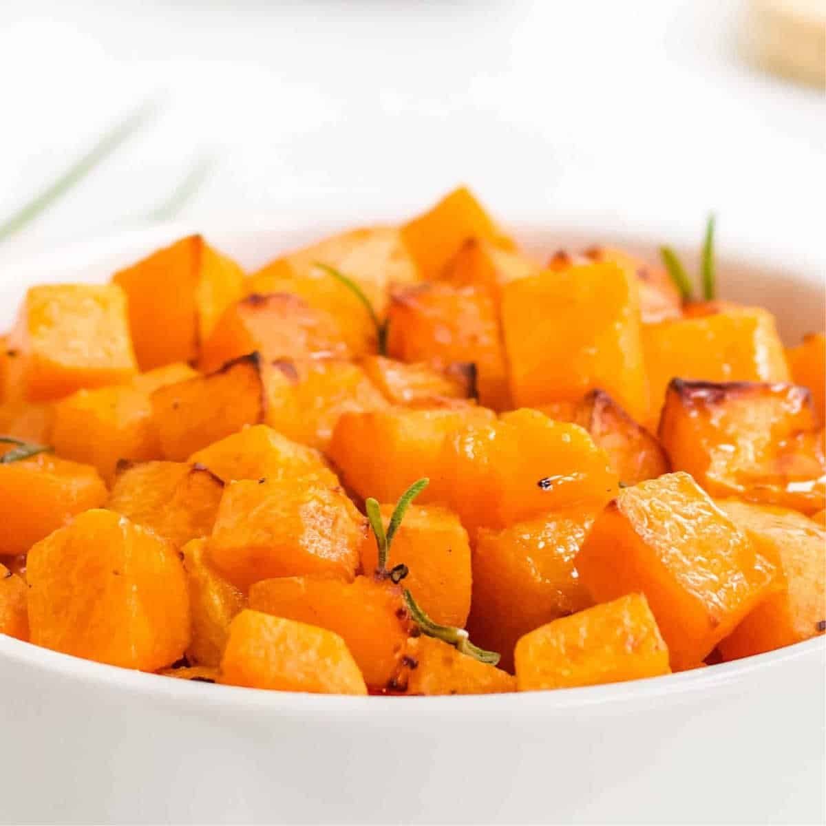 Closeup cropped bowl of air fried butternut squash with rosemary.