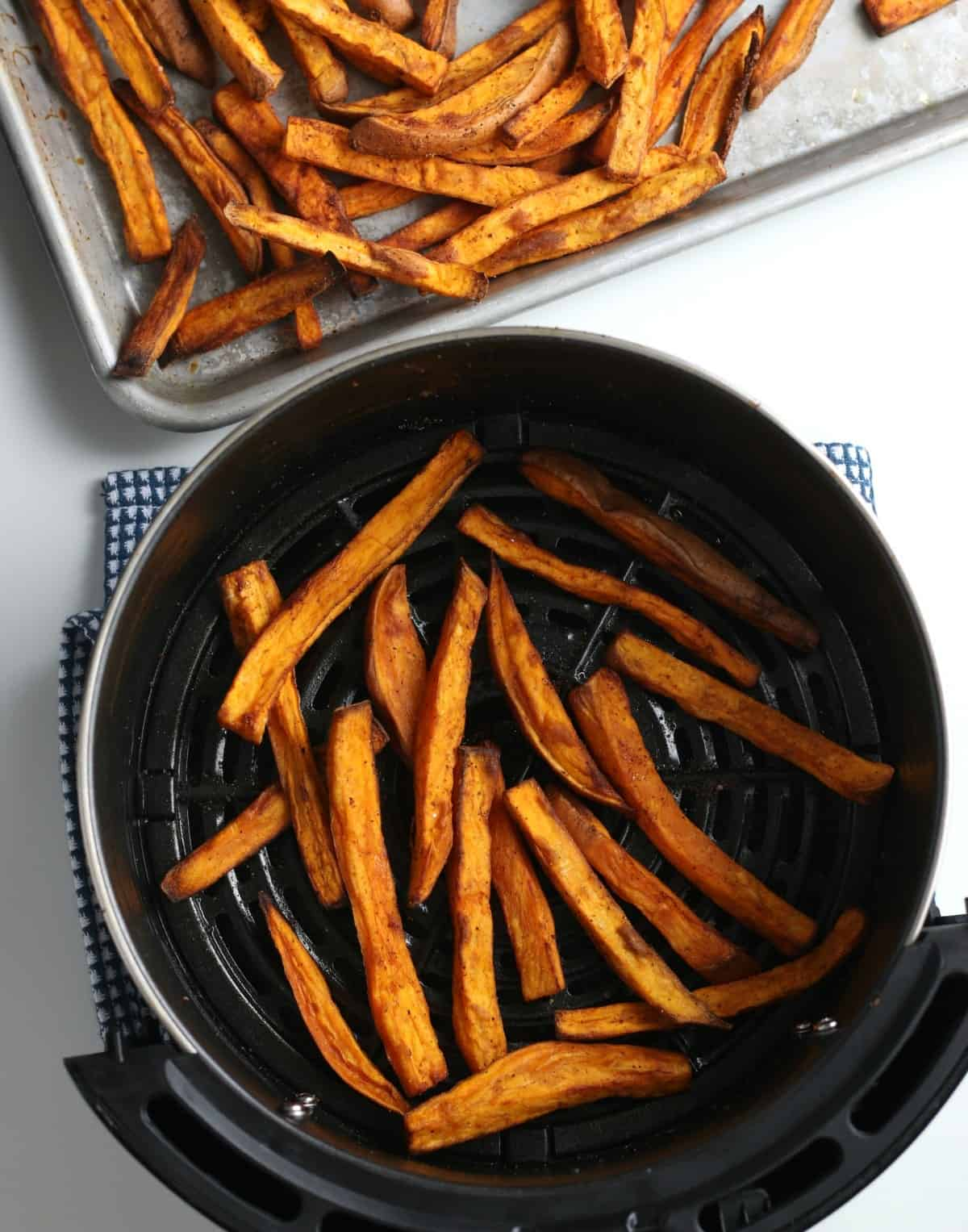 Looking down in an air fryer at cooked sweet potato fries.