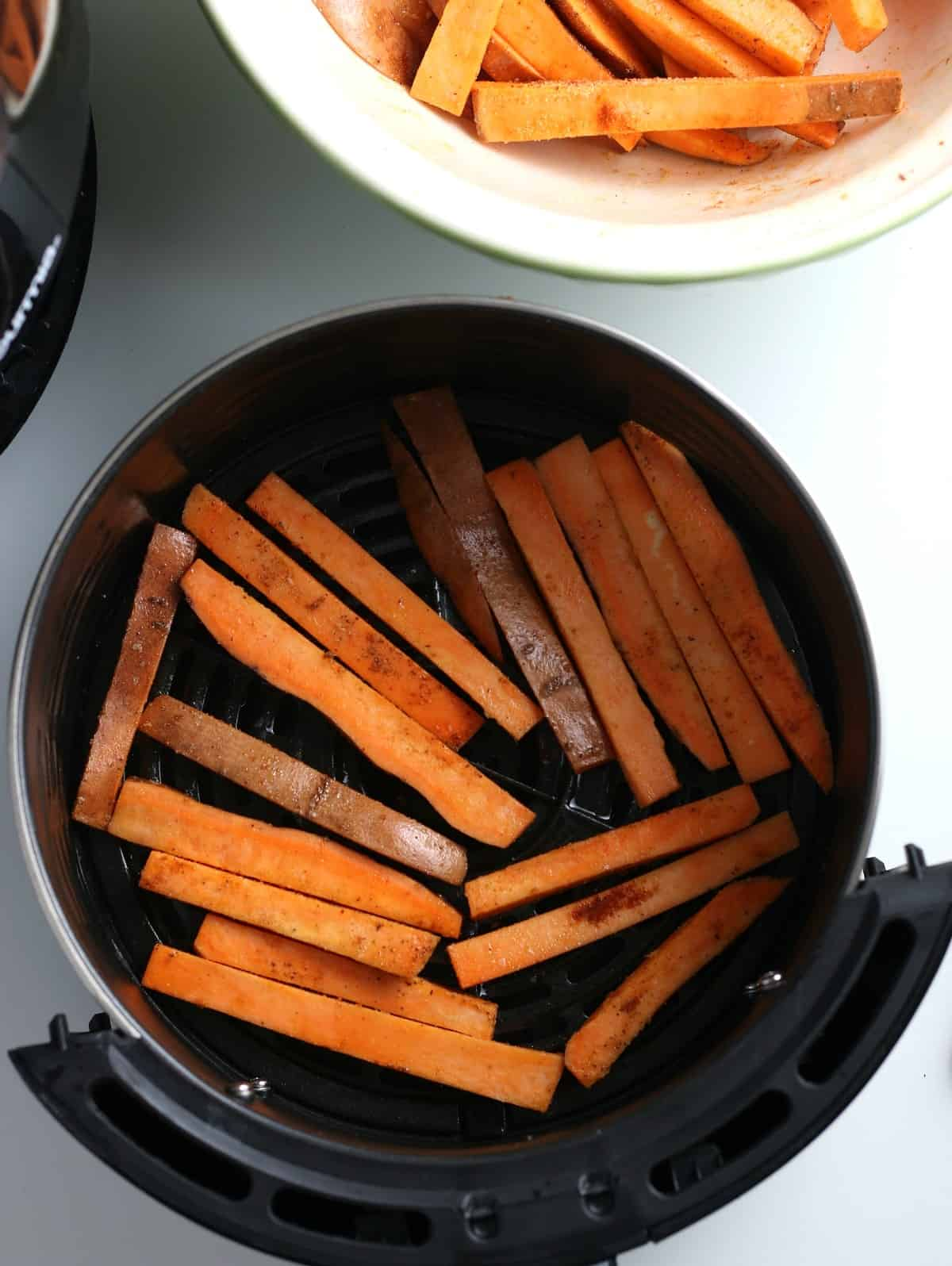Raw sweet potato matchsticks laying in the bottom of an air fryer.