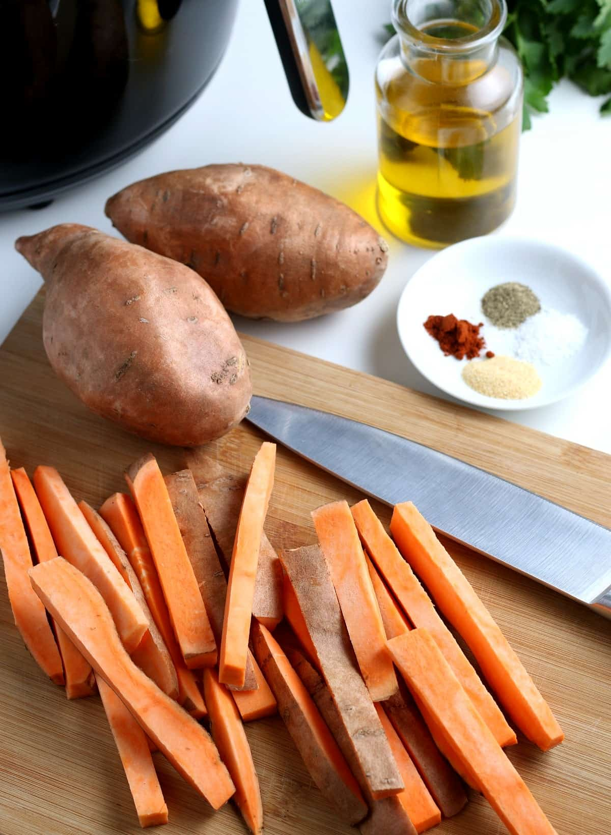 Sliced sweet potatoes in a french fry shape on a wooden board with a knife.