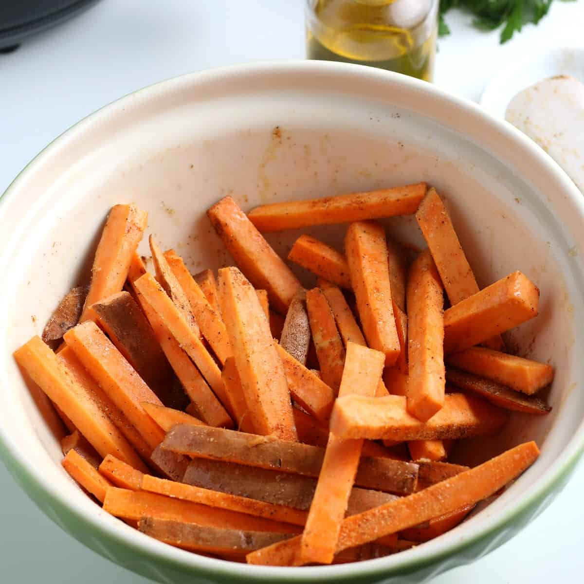 Matchstick veggies in a mixing bowl and tossed with oil and seasonings.