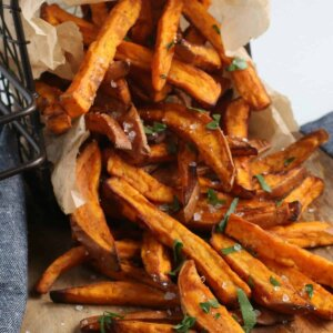 Closup of sweet potato fries dumped out on a wooden board.
