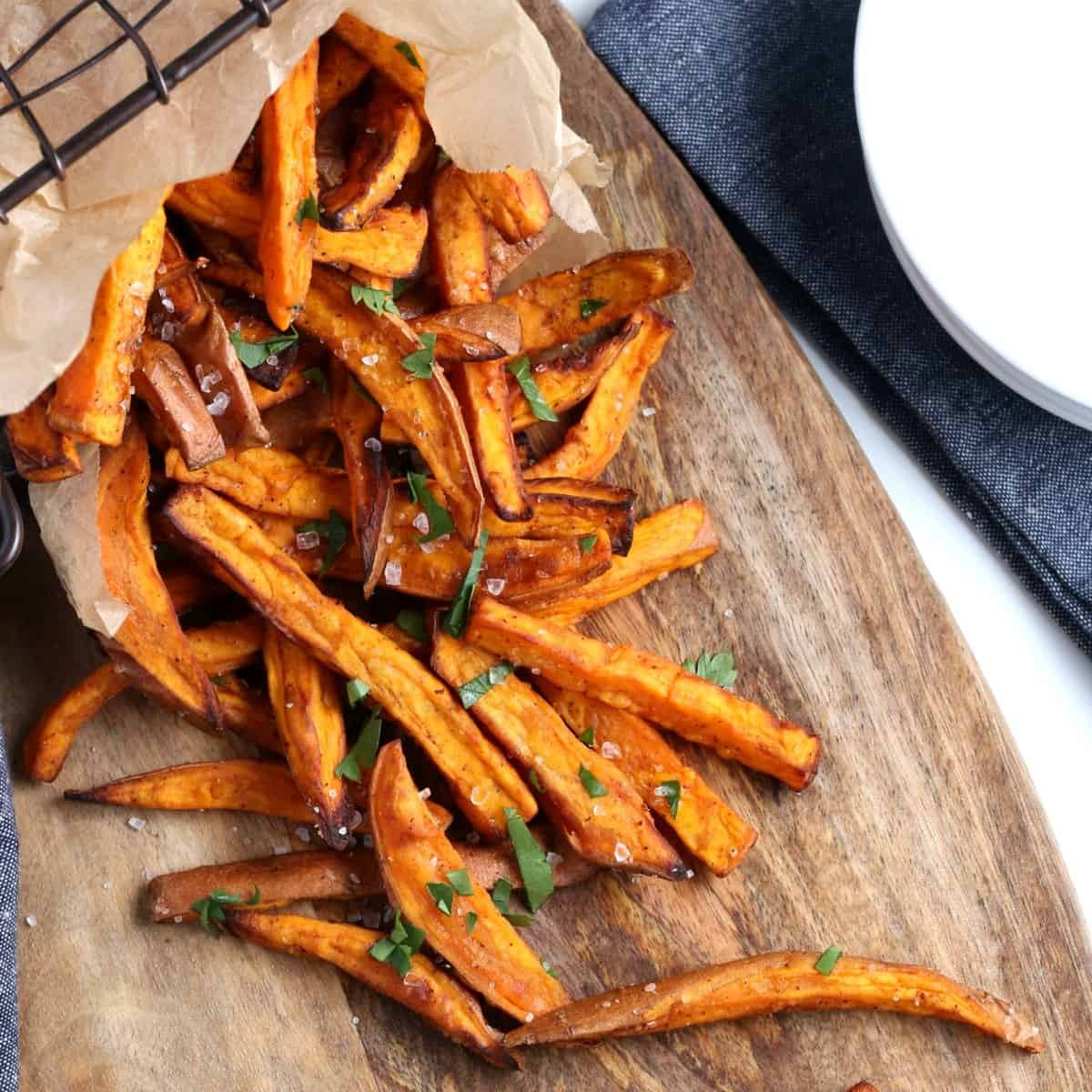 Overhead view of sprawled sweet potato fries on a wooden board.