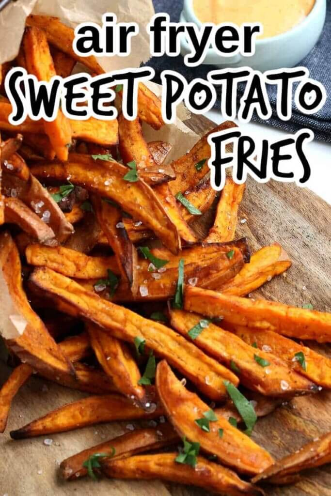 Sweet Potato Fries are spilling out onto a wooden board.