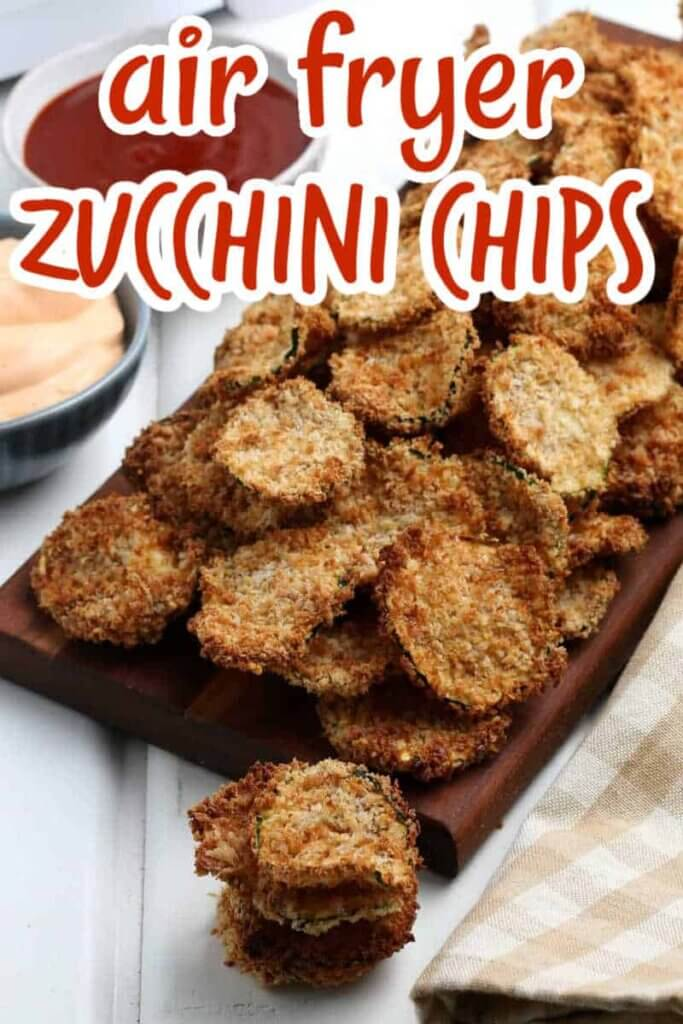 Air Fried zucchini chips piled on wooden cutting board.