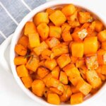 Overhead view of cooked cubed butternut squash in a white bowl.