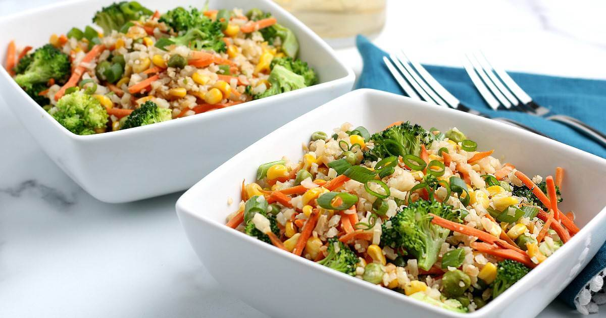 Two square white bowls filled with cauliflower rice and mixed veggies.